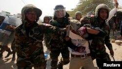 Tentara Kamboja menahan seorang pekerja dalam aksi demonstrasi di Phnom Penh, Kamis (2/1).