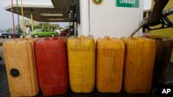 FILE- A man fills containers with diesel at a Nigeria National Petroleum Corporation petrol station in Abuja, Nigeria, May. 26, 2015.