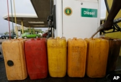 FILE- A man fills containers with diesel at the Nigeria National Petroleum Corporation, petrol station in Abuja, Nigeria, May. 26, 2015.