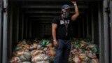 En esta fotografía del 10 de abril de 2021, un hombre espera para descargar bolsas de alimentos básicos básicos, como pasta, azúcar, harina y aceite de cocina, entregados a los residentes a través del programa de asistencia alimentaria del gobierno CLAP.