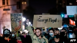 """Demonstrators attend a """"Sit Out the Curfew"""" protest against the death of George Floyd who died on May 25 in Minneapolis whilst in police custody, along a street in Oakland, California on June 3, 2020. - US protesters welcomed new charges against…"""