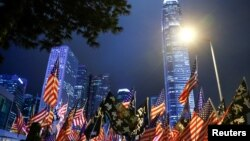 FILE - Protesters hold U.S. flags during a gathering at Edinburgh Place in Hong Kong, China, Nov. 28, 2019.