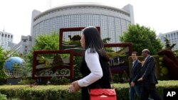 In this April 19, 2019, photo, foreigners pass by the Chinese Foreign Ministry in Beijing, China. China on Wednesday, Feb. 19, 2020 said it has revoked the press credentials of three reporters for the U.S. newspaper Wall Street Journal over a…