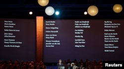 The names of the victims of Malaysian Airlines MH17 are screened during a national memorial at the RAI convention center in Amsterdam, The Netherlands, Nov. 10, 2014.