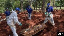 Workers bury a person believed to have died from COVID-19 at the Vila Formosa cemetery in the outskirts of Sao Paulo, Brazil, on March 31, 2020.
