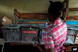 Yon dam ap lage bilten nan yon biwo'd vot nan Petyonvil, Ayiti, 25 Oktob 2015.
