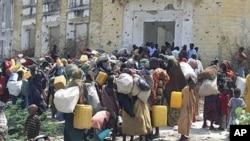 ពលរដ្ឋសូម៉ាលីស្ពាយអីវ៉ាន់រៀងខ្លួនឈរចាំនៅខាងក្រៅជំរំភៀសខ្លួនក្នុងប្រទេស នៅក្នុងទីក្រុង Mogadishu, ប្រទេសសូម៉ាលី ក្រោយពីពួកគេបានភៀសខ្លួនចេញប្រទេសសូម៉ាលីភាគខាងត្បូង ដោយការខ្វះម្ហូបអាហារនិងទឹកផឹក។ រូបថតនៅថ្ងៃទី៥ ខែកក្កដា ឆ្នាំ២០១១។