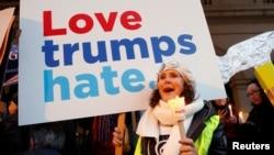 """Seorang perempuan memegang papan bertuliskan """"Love Trumps Hate"""" dan menyalakan lilin sebagai bagian dari aksi protes untuk menyuarakan Hak Perempuan """"Lights for Rights"""" saat pelaksanaan pelantikan Trump sebagai Presiden ke-45 AS, 20 Januari 2017 di depan Theatre Royal de la Monnaie, Brussels, Belgia, 20 Januari 2017."""