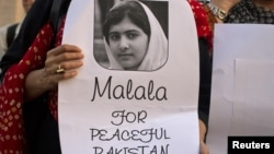 An activist from non-governmental organization Insani Haqooq Ittihad holds a picture of Malala Yousufzai during a demonstration in Islamabad, October 10, 2012.