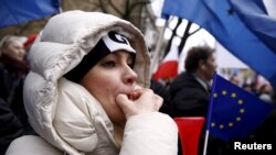 A woman whistles during an anti-government demonstration in front of the Constitutional Court in Warsaw, Poland, Dec. 12, 2015.