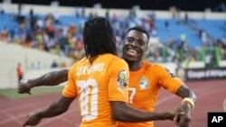 Serge Aurier, à droite, et Gervinho, à gauche, de la Côte-d'Ivoire, s'embrassent après la qualification de la sélection ivoirienne en quart de finale de la Coupe d'Afrique des Nations au détriment de l'Algérie qu'ils ont battue au stade de Malabo, Guinée équatoriale, 1er février 2015. (AP/ Dimanche Alamba)