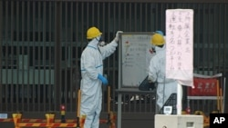 Guards read a whiteboard near the Fukushima-1 nuclear plant's main gate, Futaba, Japan
