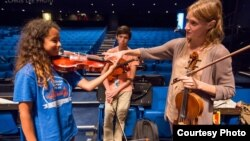 Carrie Dennis, Principal Viola with the Los Angeles Philharmonic, helps NYO-USA violist Mya Greene with her hand position. (Photo courtesy Chris Lee)