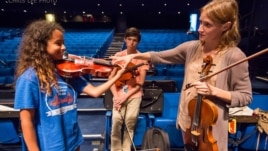 Carrie Dennis, Principal Viola with the Los Angeles Philharmonic, helps NYO-USA violist Mya Greene with her hand position. (Photo courtesy Chris Lee)