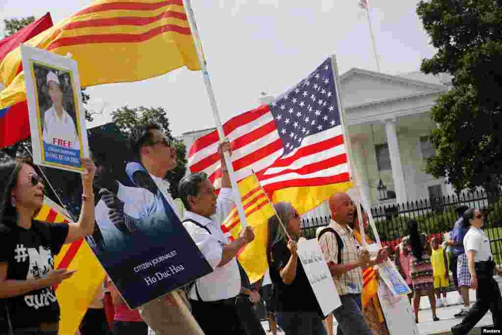 Người biểu tình cầm cờ Việt Nam Cộng hòa và quốc kỳ Mỹ cùng biểu ngữ phản đối chuyến viếng thăm của ông Nguyễn Phú Trọng bên ngoài Tòa Bạch Ốc.