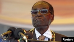 FILE: President Robert Mugabe waits to address crowds gathered for Zimbabwe's Heroes Day commemorations in Harare, August 10, 2015.