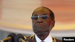 FILE - President Robert Mugabe waits to address crowds gathered for Zimbabwe's Heroes Day commemorations in Harare, August 10, 2015.