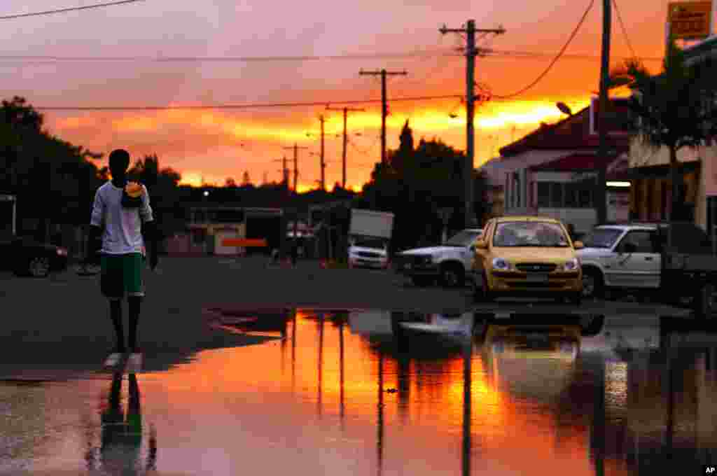 Jan. 6: A man arrives at flooded waters at Depot Hill in Rockhampton, Queensland, Australia. Queensland's record floods are causing catastrophic damage to infrastructure and have forced 75 percent of its coal mines, which fuel Asia's steel mills, to be ha