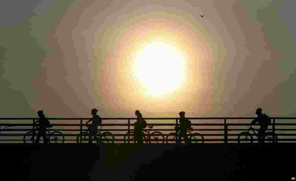 Commuters walk their bicycles across a pedestrian bridge, in Bogota, Colombia.
