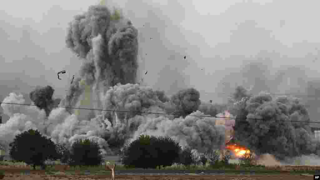 Thick smoke, debris and fire rise following an airstrike by the U.S.-led coalition in Kobani, Syria as fighting intensified between Syrian Kurds and the militants of Islamic State group, as seen from Mursitpinar on the outskirts of Suruc, at the Turkey-Syria border, Sunday, Oct. 12, 2014.