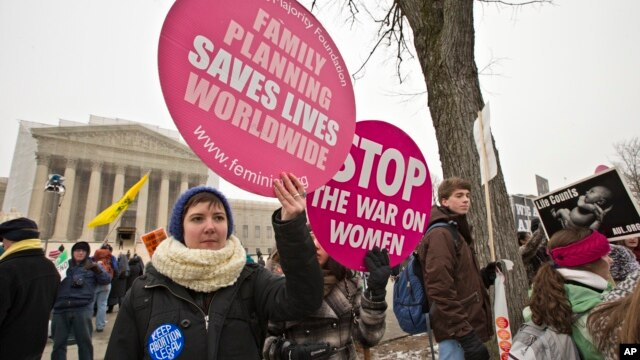 Abortion rights protesters hold signs as anti-abortion activists march past the Capitol to the Supreme Court in Washington, Jan. 25, 2013.