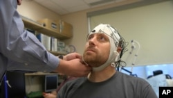In this Nov. 20, 2019 image from video, Zach Ault is fitted with an EEG cap which uses electrodes to track the electrical activity of his brain, at the National Institutes of Health's hospital in Bethesda, Md. (AP Photo/Federica Narancio)