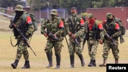 FILE - Defected members of the Colombian guerrilla group ELN walk to a military base to surrender and handover their weapons, in Cali, July 16, 2013.
