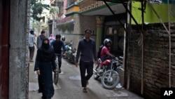 人们走过纽约地铁炸弹袭击案嫌疑人乌拉曾在孟加拉国达卡居住的楼房。(2017年12月12日)