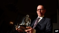 In this photo taken Wednesday, Oct. 17, 2018., the head of BIPM (International Bureau of Weights and Measures) Martin J.T. Milton holds a replica of the International Prototype Kilogram in Sevres, near Paris. (AP Photo/Christophe Ena)