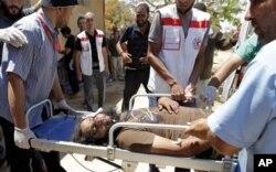Des secouristes trasportant un rebelle libyen blessé, dimanche, au front près de Misrata