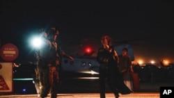 資料照片:2021 年 8 月 15 日,一名海軍陸戰隊員在阿富汗喀布爾的哈米德·卡爾扎伊國際機場護送一名攜帶兒童疏散的國務院僱員。