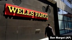 FILE - A man passes by a Wells Fargo bank office in Oakland, Calif., July 14, 2014.