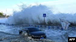 A car sits in floodwaters as waves, caused by Typhoon In-Fa further down the Chinese coast, surge over a barrier along the seacoast in Qingdao in China's eastern Shandong province July 25, 2021.