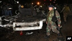 Lebanese army soliders stand guard near damages after a suicide bomber blew himself up in a passenger van in the Choueifat district in southern Beirut, Feb. 3, 2014