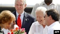 Phu nhân Rosalynn, trái, và cựu Tổng thống Mỹ Jimmy Carter nhận được một bó hoa khi đến sân bay Marti Jose ở Havana, 28/3/2011