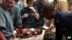 Medical professionals aboard the Military Sealift Command hospital ship USNS Comfort (T-AH 20) treat a six-year-old Haitian boy in the casualty receiving room aboard the 1,000-bed hospital ship.