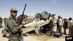 Một binh sĩ Tunisia đứng gác gần 1 chiếc xe bị lật thuộc phe ông Gadhafi sau vụ đụng độ gần biên giới Libya và Tunisia, 29/4/2011