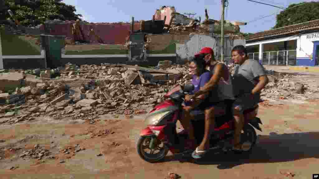 Trois personnes sur une moto conduisent près d'un bâtiment effondré, au Mexique, le 8 septembre 2017.