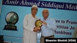 سینیٹر فرحت اللہ بابر پشاور پریس کلب میں سینیر صحافی ثنااللہ خان کو لالہ امیر احمد صدیقی ایوارڈ دے رہے ہیں۔ 7 اپریل 2018