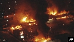 FILE - In this April 29, 1992 file photo, several buildings in a shopping center are in flames before firefighters can arrive as rioting erupted in South-Central Los Angeles following the acquittal of four police officers in the videotaped beating of Rodney King. (AP Photo/Reed Saxon, File)