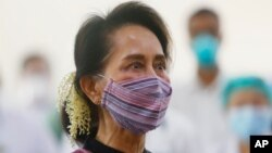 FILE - Myanmar leader Aung San Suu Kyi watches the vaccination of health workers at a hospital in Naypyitaw, Jan. 27, 2021.