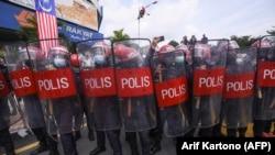 Polisi Federal Reserve Unit (FRU) memblokir jalan menuju gedung parlemen ketika anggota parlemen oposisi Malaysia berusaha berbaris di parlemen untuk memprotes penutupannya di Kuala Lumpur pada 2 Agustus 2021. (Foto: AFP/Arif Kartono)