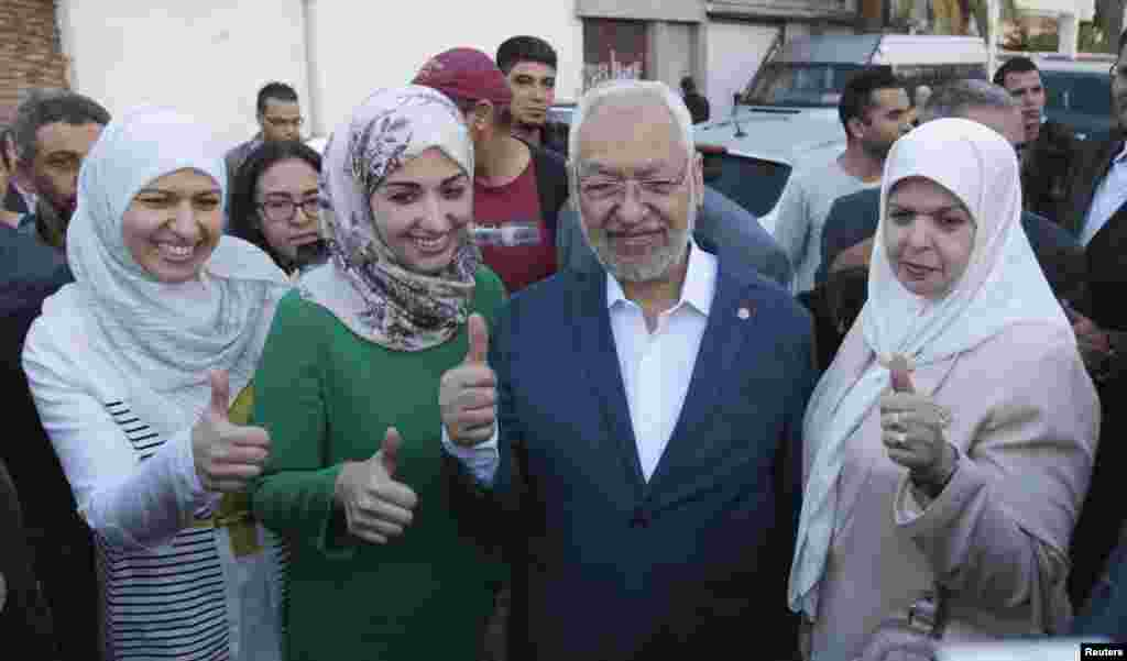 Rached Ghannouchi, leader of the Tunisian Islamist party Ennahda, gestures with his wife and two daughters Yousra (left) and Soumaya (2nd left) at a polling station in Tunisia, Oct. 26, 2014.