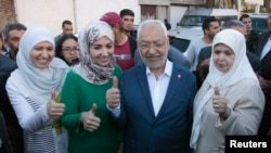 Rached Ghannouchi (C), leader of the Tunisian Islamist party Ennahda, gestures with his wife and two daughters Yousra (L) and Soumaya (2nd L) at a polling station during an election in Tunisia October 26, 2014.Tunisians voted on Sunday in parliamentary el