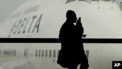 Un viajero habla desde su móvil dentro de un aeropuerto. Pronto podría quedar a discreción de las líneas áereas permitir llamadas dentro de los aviones.