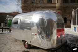 Shiny Airstreams come in all sizes. Here's a tiny one. Kind of doubt this one has all the comforts of home.