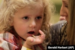 In this Nov. 11, 2011 photo, Corinne Hufft, right, of Dallas, feeds her daughter Ella Hufft, 3, a boiled mealworm as visitors sample Thanksgiving-inspired foods with insects at the Audubon Insectarium in New Orleans. (AP Photo/Gerald Herbert)