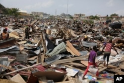 FILE - Residents salvage objects from houses demolished by government officials in Otodo-Gbame waterfront in Lagos Nigeria, March.18, 2017.