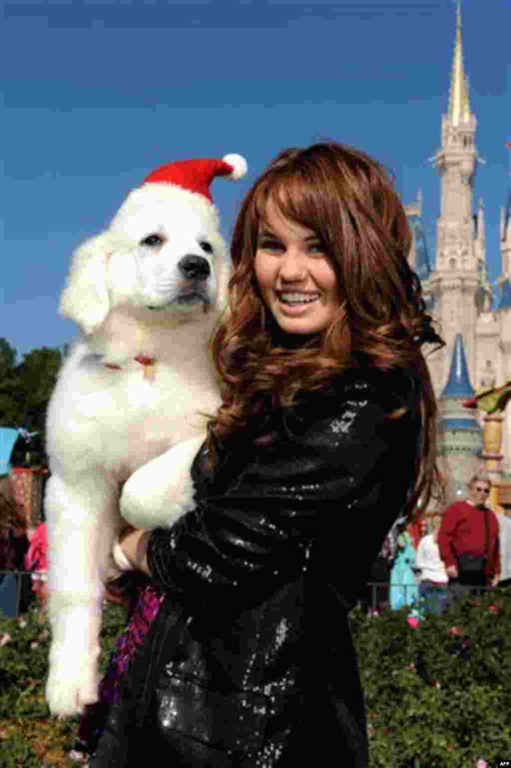 """In this publicity image released by Disney, actress and singer Debby Ryan, star of Disney Channel's """"The Suite Life on Deck,"""" with the canine star of the new Disney holiday movie """"The Search for Santa Paws"""" on Thursday, Dec. 2, 2010 while taping a segmen"""