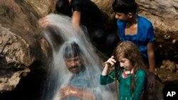 ARSIP - Sebuah keluarga mendinginkan diri di sungai selama gelombang panas yang melanda, di Islamabad, Pakistan, tanggal 30 Mei 2017. Kota Turbat di baratdaya Pakistan mencatat suhu setinggi 54 derajat Celsius pada bulan Mei (foto: B.K. Bangash/AP Photo)